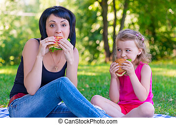 Mom and daughter eating tasty burgers on a picnic