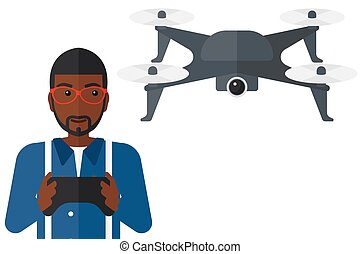 Man flying drone. - An african-american man flying drone...