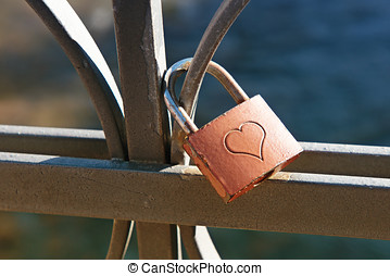 Love lock engraved with a heart to signify commitment and...