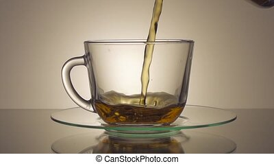 Tea being poured into glass tea cup in slow motion
