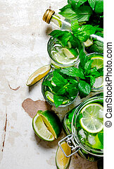 The concept of cocktail with lime, mint, rum on the old background .