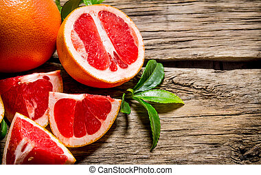 Fresh cut grapefruit with leaves. On wooden table.