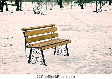 Lonely Bench in the Park Covered by Snow in Winter
