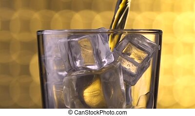 glass with ice cubes and pouring whiskey