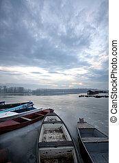 Danube - old boat on frozen river Danube in january