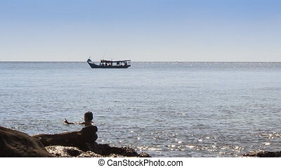 People Swim in Sea by Rock Beach Boat Drifts past - PHU...