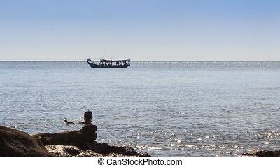 People Swim in Sea by Rock Beach Boat Drifts past