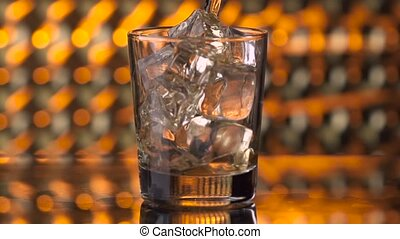 Pouring whiskey into glass with ice cubes
