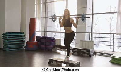 A muscular woman athlete performs back lunges with weights on a barbell step platform in the gym.