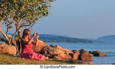Blond Girl in Red Sits on Beach Takes Photo at Sunset by Rocks