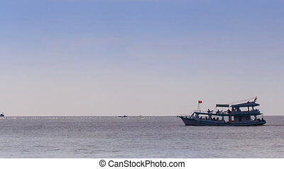 Vietnamese Tourist Boat Drifts along Sea Skyline - large...
