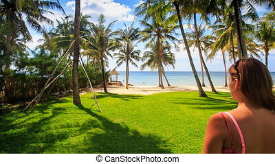 Closeup Blond Girl in Red Walks to Beach along Lawn in Palm...