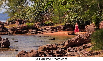 Blond Girl in Red Walks by Rocks along Beach with Plants