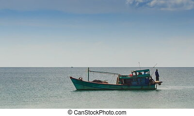 Vietnamese Fishing Boat Man on Stern Drifts along Sea -...