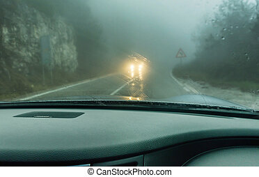 View through the cars windshield in the winter fog on the...