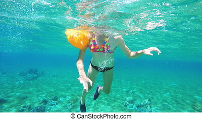 Young girl scuba diver and coral.Group of coral fish in blue...