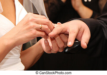 The woman dresses a wedding ring on a finger to the man -...