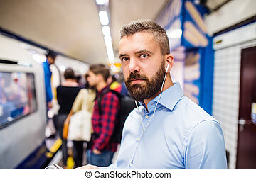 Young man in subway - Young handsome man standing on subway...