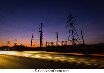 silhouette electricity pylons and power plant with light...