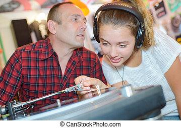 Man talking to girl playing vinyl record