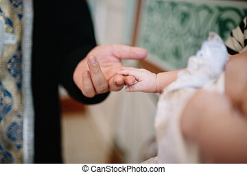 holding baby hand during christening