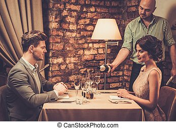 Waiter pouring sparkling wine into glasses to restaurant...