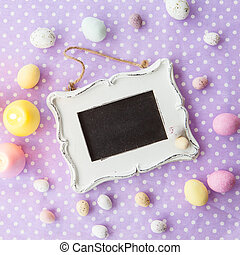 Easter background - Candy easter eggs on purple polka dot...