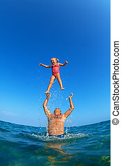 Man tossing up child with water splashes in beach -...