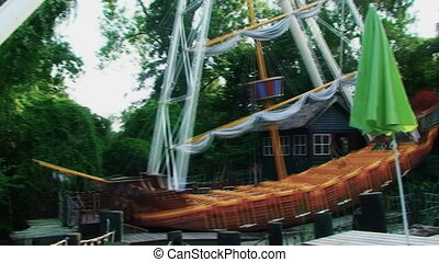 An amusement Park, a large swing in the form of a ship...