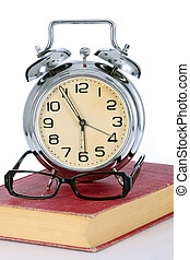 book with alarm clock and eyeglasses on white background