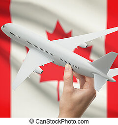 Airplane in hand with flag on background - Canada - Airplane...