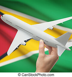 Airplane in hand with flag on background - Guyana - Airplane...