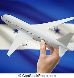 Airplane in hand with flag on background - Honduras -...