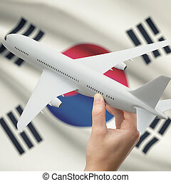 Airplane in hand with flag on background - South Korea -...