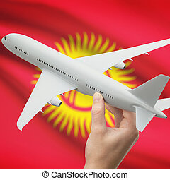 Airplane in hand with flag on background - Kyrgyzstan -...