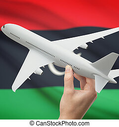 Airplane in hand with flag on background - Libya - Airplane...