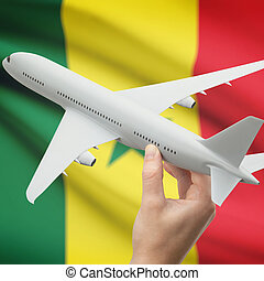Airplane in hand with flag on background - Senegal -...
