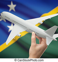 Airplane in hand with flag on background - Solomon Islands -...