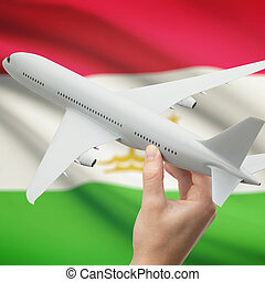 Airplane in hand with flag on background - Tajikistan -...