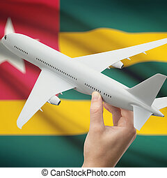 Airplane in hand with flag on background - Togo - Airplane...