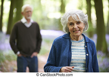 Senior Couple Walking Through Bluebell Woods