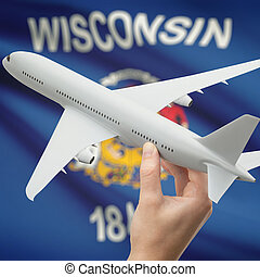 Airplane in hand with US state flag on background - Wisconsin