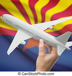 Airplane in hand with US state flag on background - Arizona...