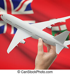 Airplane in hand with Canadian province flag on background -...