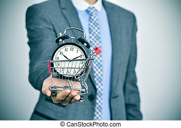 businessman with an alarm clock in a shopping cart - a young...