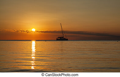 ocean sunset with boat sailing