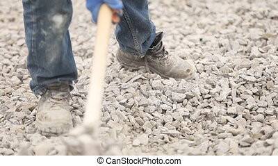 Worker distributes gravel - Worker distributes manual...