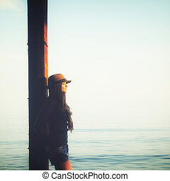 Casual girl relaxing under the pier in a sea water, enjoy sunset light and breathing air.