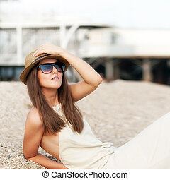Happy fashion dressed woman in hat rest sitting on a beach....