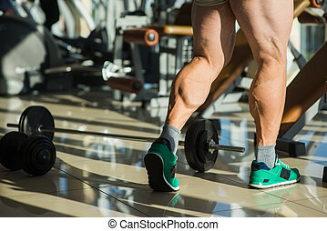 Strong man's legs. Sportsman in gym. Dumbbell and barbell on...